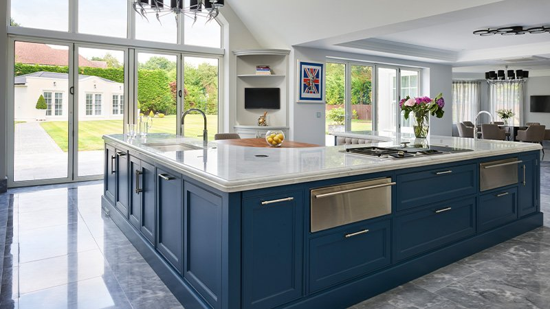 large kitchen island with a large range cooker under a hand painted canopy extractor