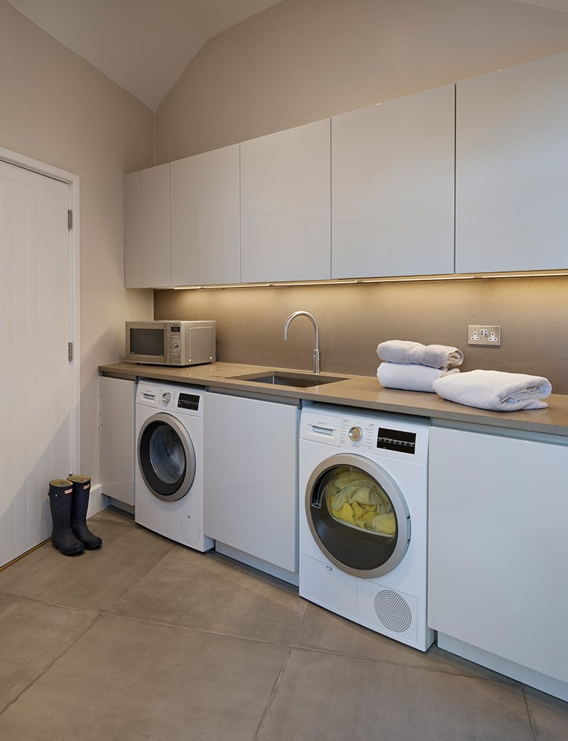 utility room with kitchen appliances and lots of storage cupboards