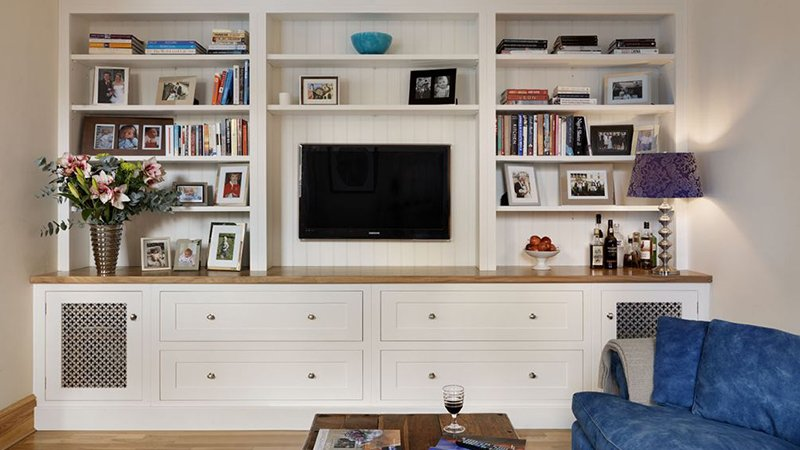 wall mounted tv surrounded by shelves